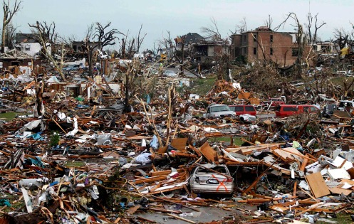Destroyed vehicles and buildings litter a neighborhood after a devastating tornado hit Joplin
